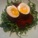 Beet Salad tossed in an Anchovy Infused Balsamic Dressing, served on a Bed of Baby Arugula and topped with a Farm Fresh Soft Boiled Egg